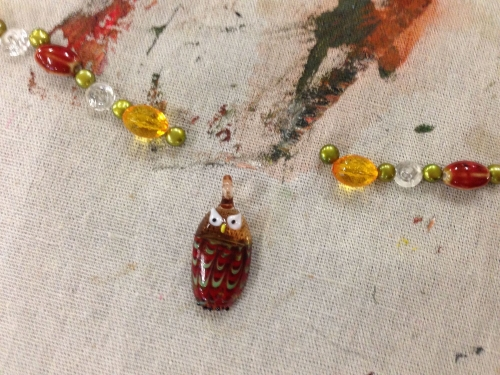 Shandell creates a pattern of beads for his wise owl necklace.