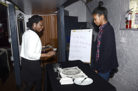A YLOT participant receives   a lesson in table setting and etiquette/ Photo courtesy of Young Ladies of Tomorrow
