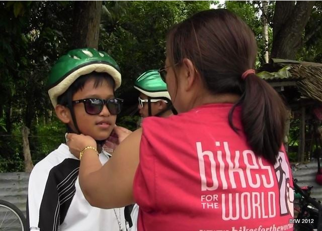 In the Philippines, a BfW volunteer fits a child with a helmet./  Photo courtesy of Bikes for the World