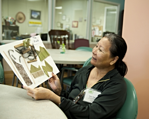 An artist admires her work at Alexandria Adult Day Services Center. (Photo Stephanie Williams)/Photo source: AFTA