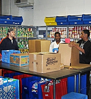 The  volunteers  at Manna Food Center pack boxes to distribute more than 16,000 pounds of food each day, according to Manna's 2014  annual report .
