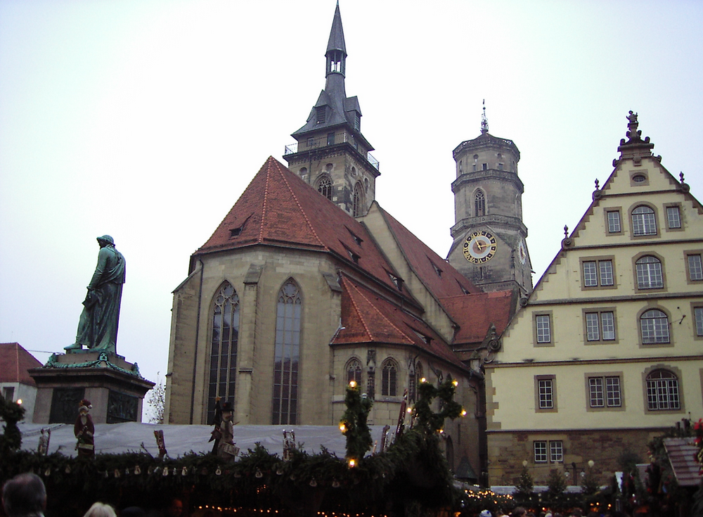 The Stiftskirche, Stuttgart. View from the rear of the church, dissimilar towers in view. At left is a(n unrelated) statue of Schiller, surrounded by Christmas market stuff. Wikimedia Commons photograph by Joachim Köhler.