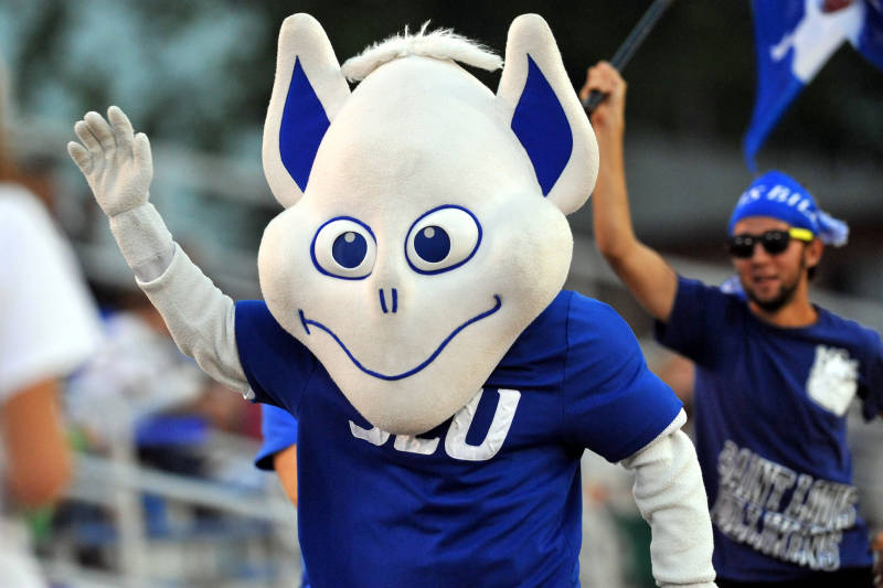 The last iteration of the Billiken, here given three-dimensional form as a courtside costume. Photography credit unavailable (SLU Athletics, 2012). I wrote in 2010: Look at that meandering mouth, the blank yet slightly cross-eyed gaze. Doesn't he look like he's trying to pass a sobriety test? Does he have any hope of intimidating an opponent? Of course not–he's trying to touch his nose! On the positive side, he's got enviable sneakers, and his italicized SLU seems slightly aggressive.