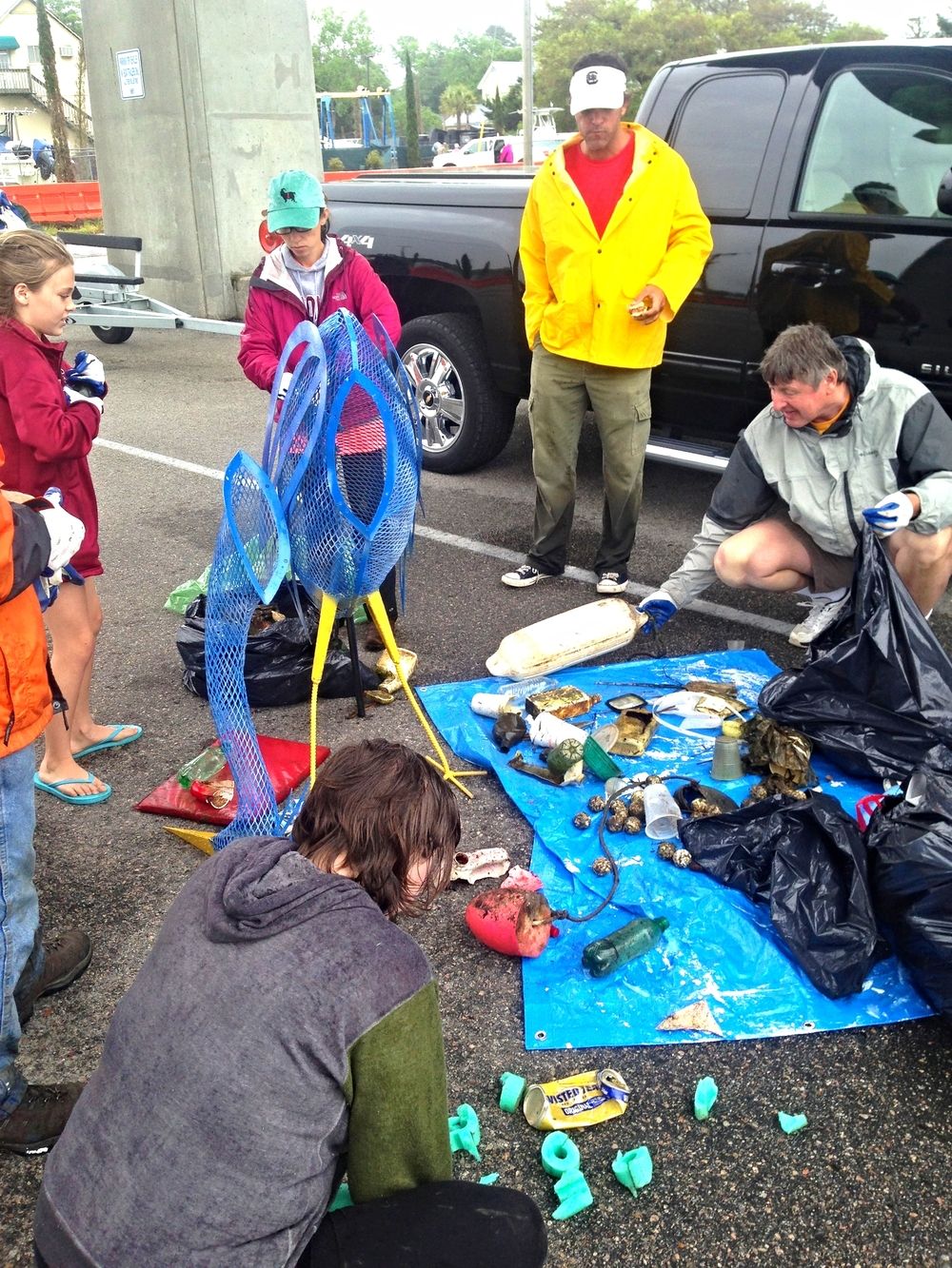 Volunteers at the Little River Sweep choose items to go inside the blue heron