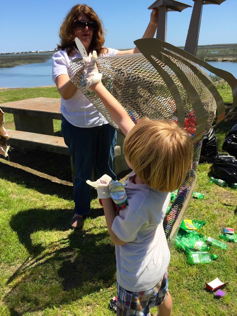 A 7 year old fills the morse Park Pelican with Crushed bottles and cans