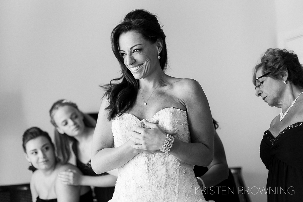 The bride's 2 daughters admire their mother as she beams just after slipping into her gown.