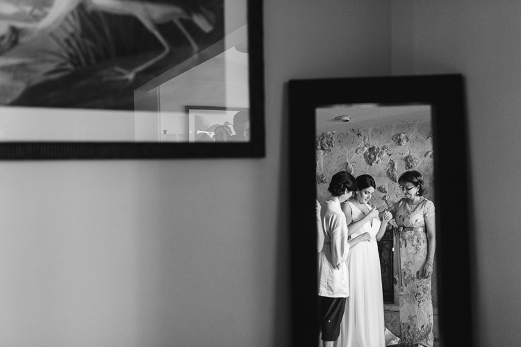 Bride putting on dress documentary style photography