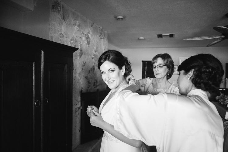 Bride zipping up dress at Coconut Palm Inn in Tavernier, Fl