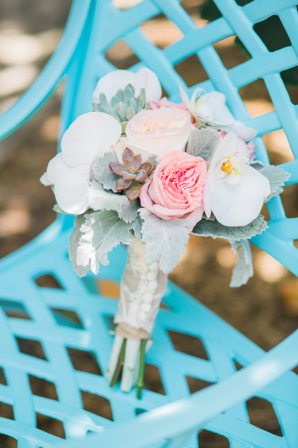 Coastal bouquet sits on teal chair at River Palm Cottages in Jensen Beach, Fl