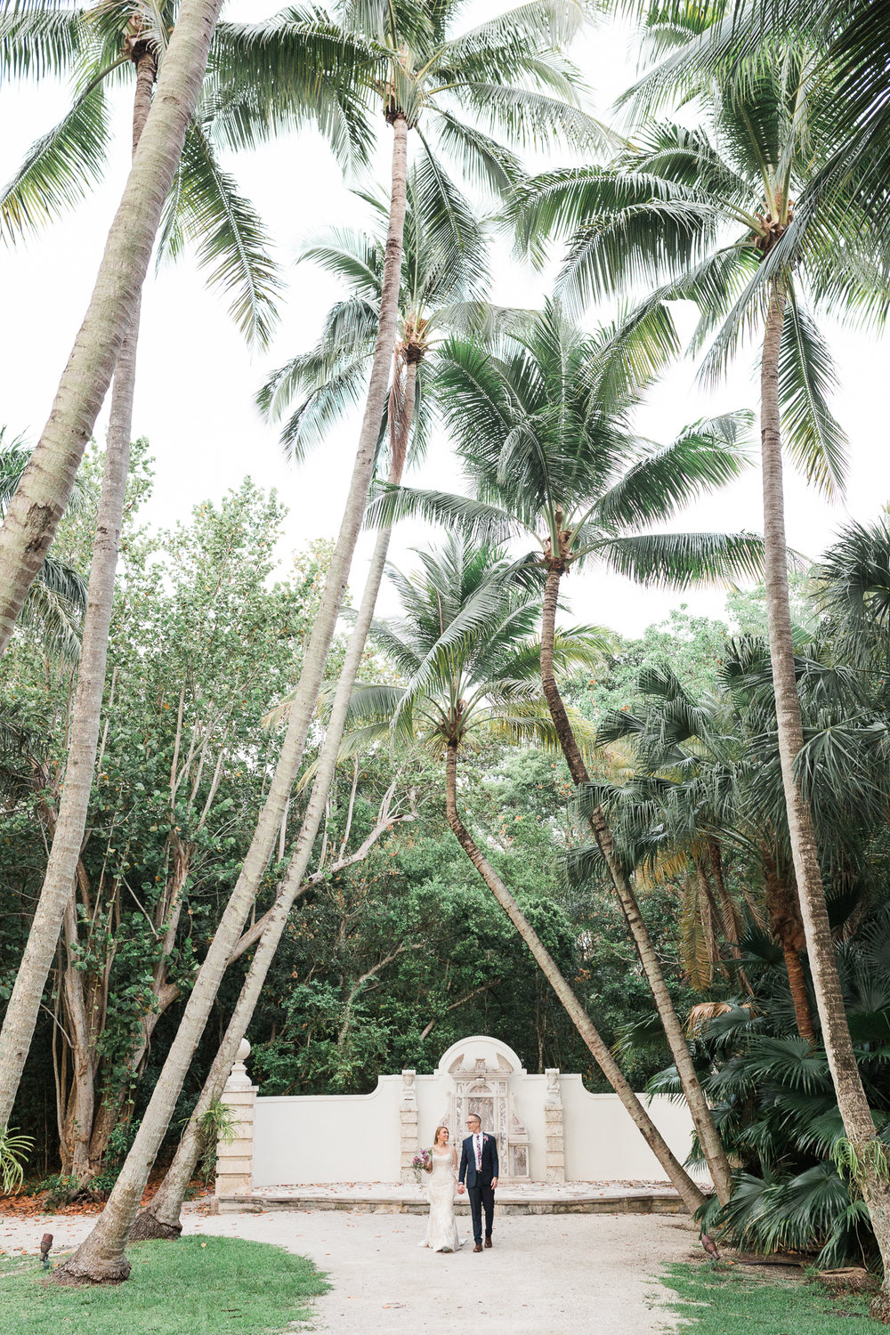 Bride and groom hold hands beneath the palm trees at Bonnet House