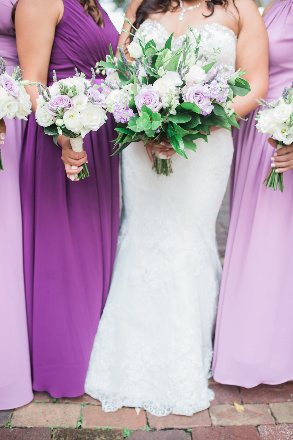 Bride and bridesmaids hold flowers wearing purple dresses at Casa Feliz