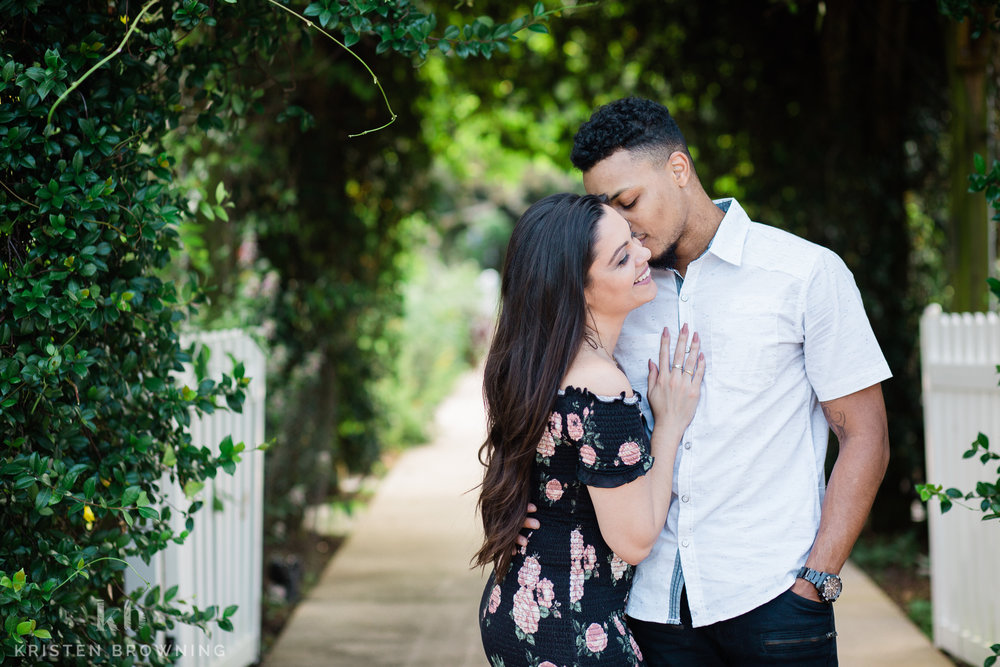 Photo of guy kissing girl on the cheek with greenery in Port St. Lucie Botanical Garden