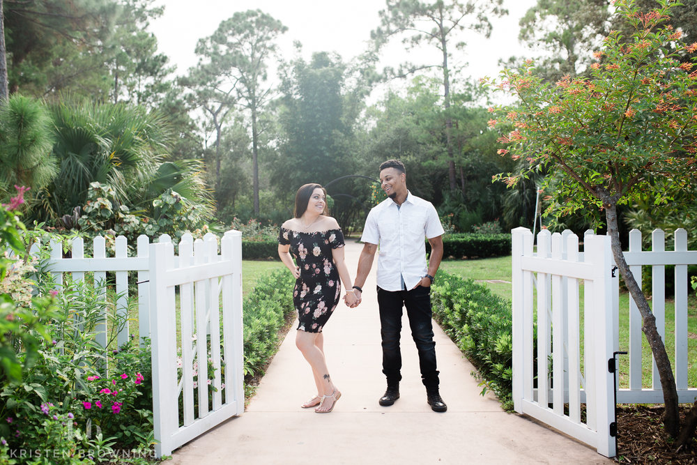 engagement photo of couple holding hands in front of a white picket fence with greenery and flowers behind them at PSL Botanical Gardens