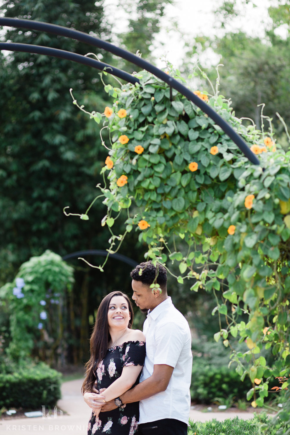 couple standing beneath an arbor with yellow flowers at PSL Botanical Gardens for engagement session