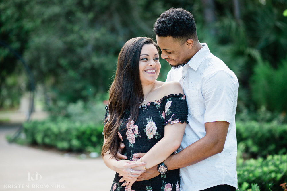 couple embracing with greenery behind them at PSL Botanical Gardens for engagement session