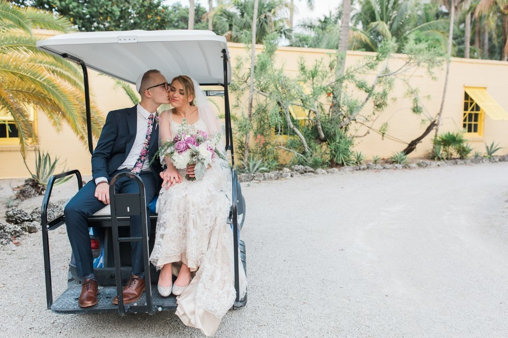 Groom kisses bride on cheek while on golf cart at The Bonnet House