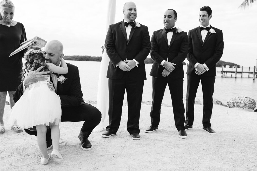 Groom hugs flower girl at Coconut Palm Inn Wedding