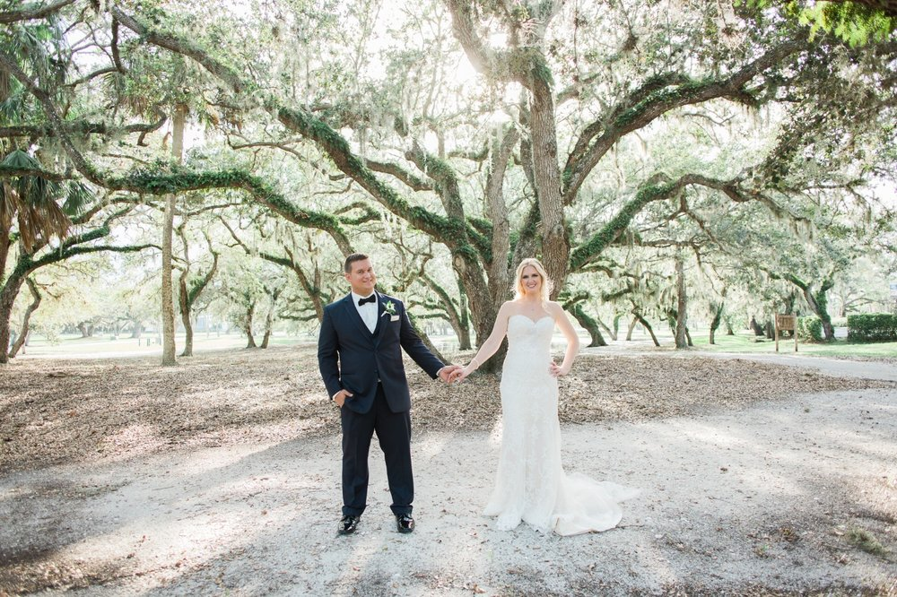 Bride and groom hold hands under oak trees at Riverside Park in Vero Beach, FL