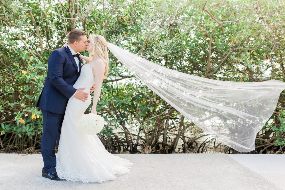 Bride and groom kiss as floor length veil blows in the wind in Vero Beach, FL