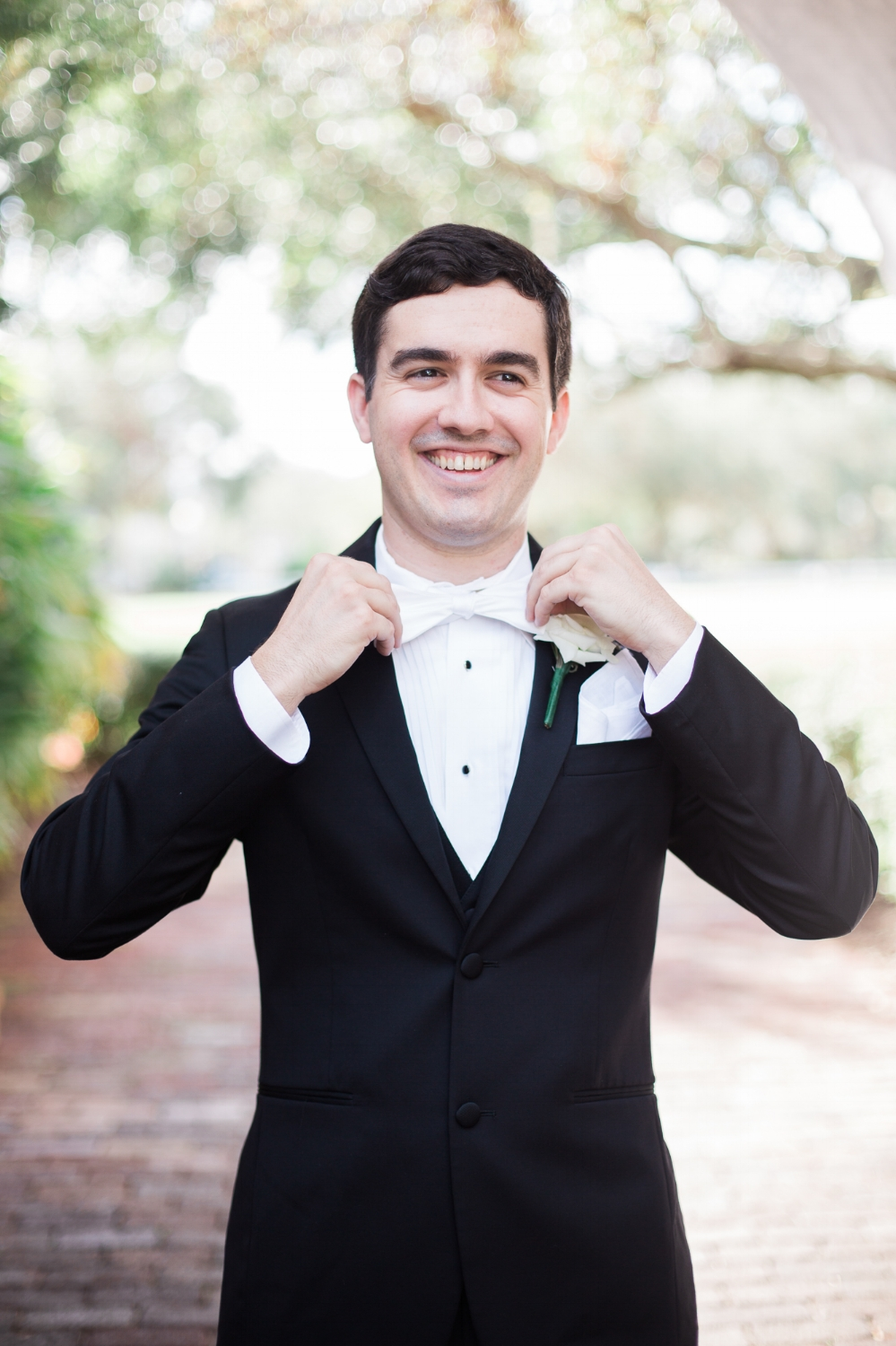 Groom adjusts bow tie at Casa Feliz in Winter Park, FL