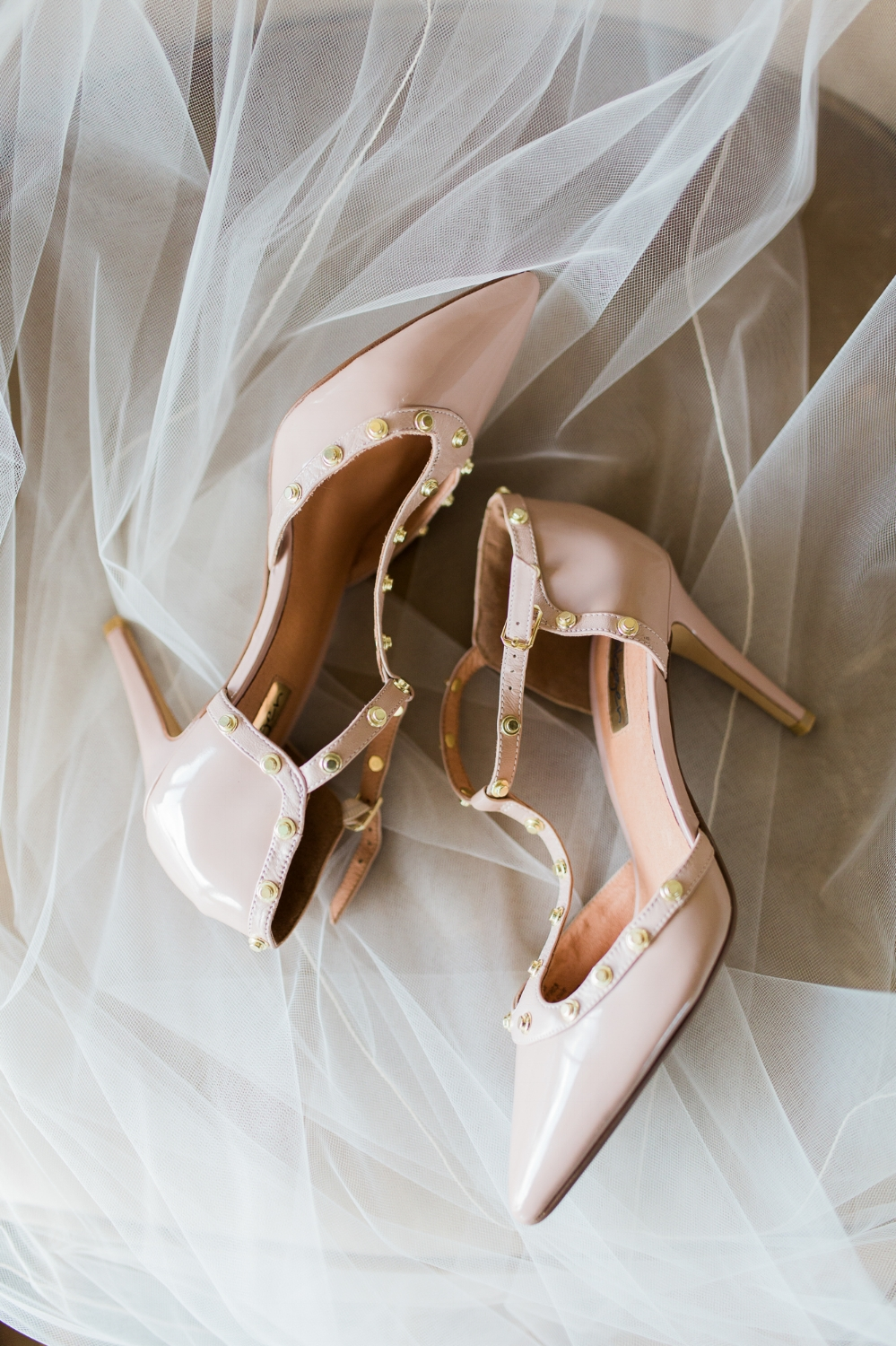 Blush colored wedding shoes lay on top of veil