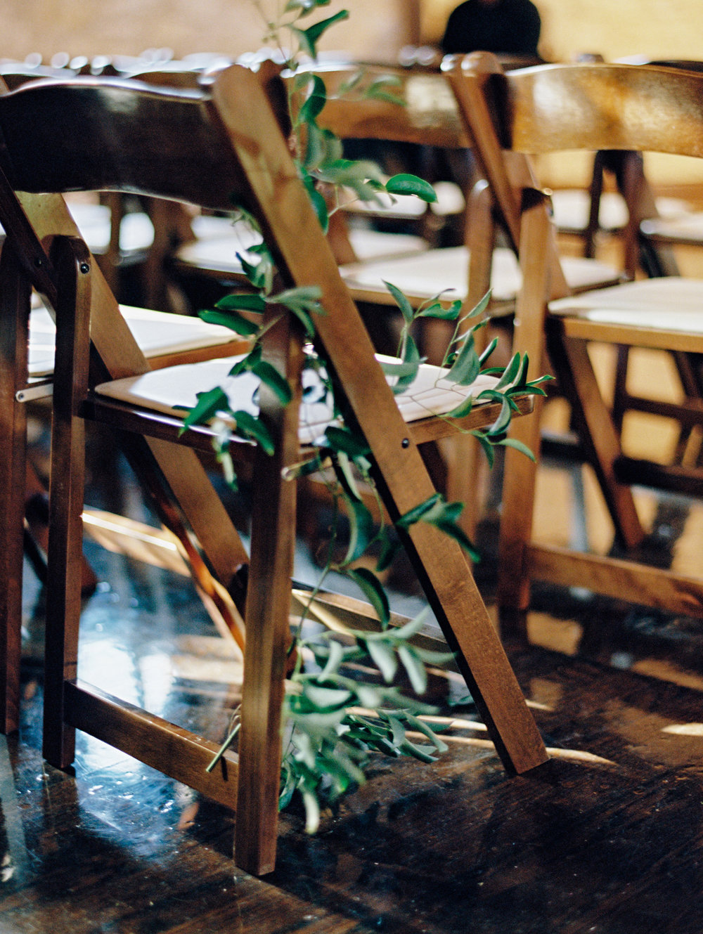 The smallest green leaves adorn these wooden reception chairs. | The Wildflowers featured on Martha Stewart Weddings | Instagram: @ thewildflowers_com | www.thewildflowers.com