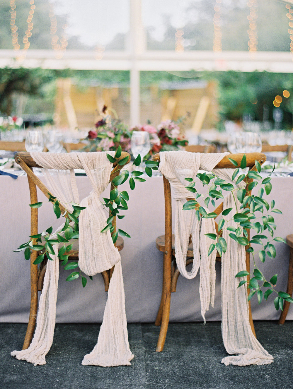 The bride and groom's chairs were decorated with looped linen and bunches of greens. | The Wildflowers featured on Martha Stewart Weddings | Instagram: @ thewildflowers_com | www.thewildflowers.com