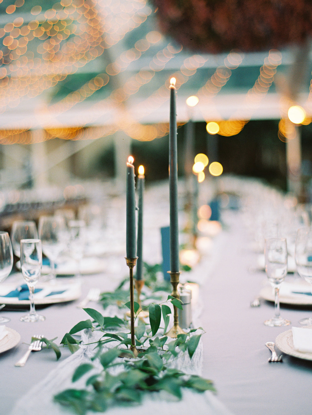 Tall forest green candles are elegant when surrounded by greenery. | The Wildflowers featured on Martha Stewart Weddings | Instagram: @ thewildflowers_com | www.thewildflowers.com
