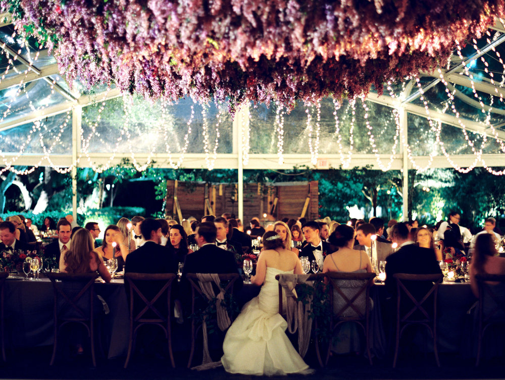 Twinkling lights illuminate a freesia installation above a bride and her guests. | The Wildflowers featured on Martha Stewart Weddings | Instagram: @ thewildflowers_com | www.thewildflowers.com