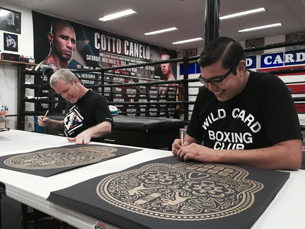 Freddie Roach and Ernesto Yerena Montejano signing prints together at Wild Card Boxing Club in Hollywood, CA.