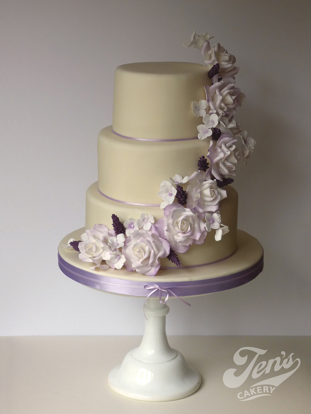 A wedding cake with a cascade of sugar roses and lavender