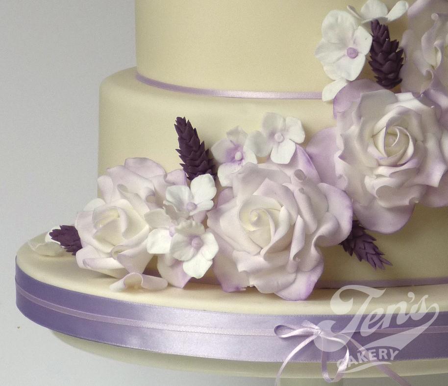 A wedding cake with a cascade of sugar roses