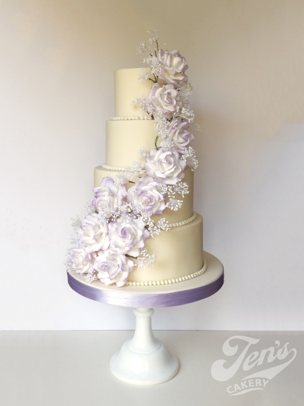 A wedding cake with a cascade of sugar roses ang gypsophilia or baby's breath.