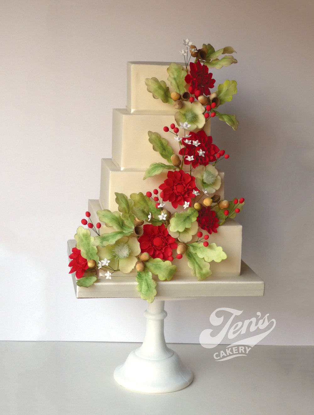A square wedding cake with a cascade of green foliage and red crysanthamums.