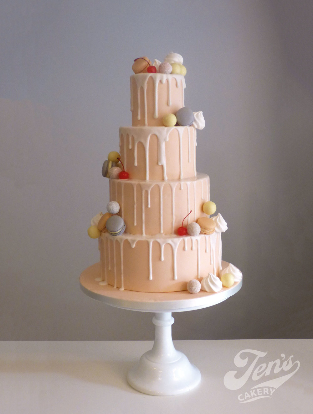 Blush peach drip wedding cake with white icing drizzles, meringues and truffles.