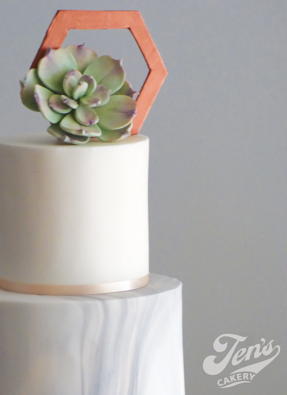 Wedding cae with copper sequins, marble and succulents. The metallic tier could also be gold, silver, bronze, or rose gold.