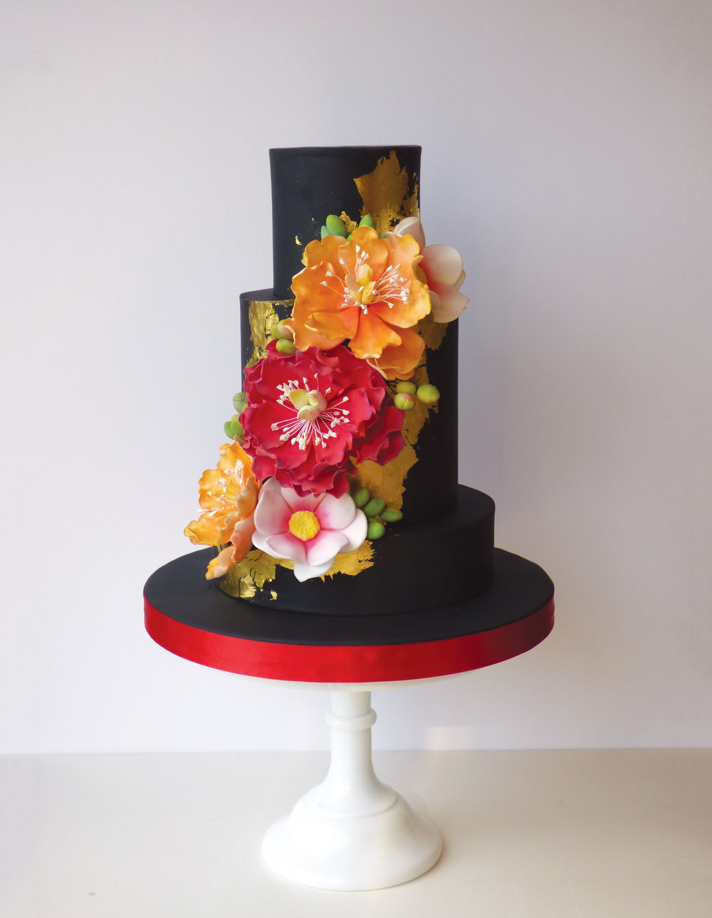 A luxurious, elegant wedding cake with gold leaf and sugar flower art