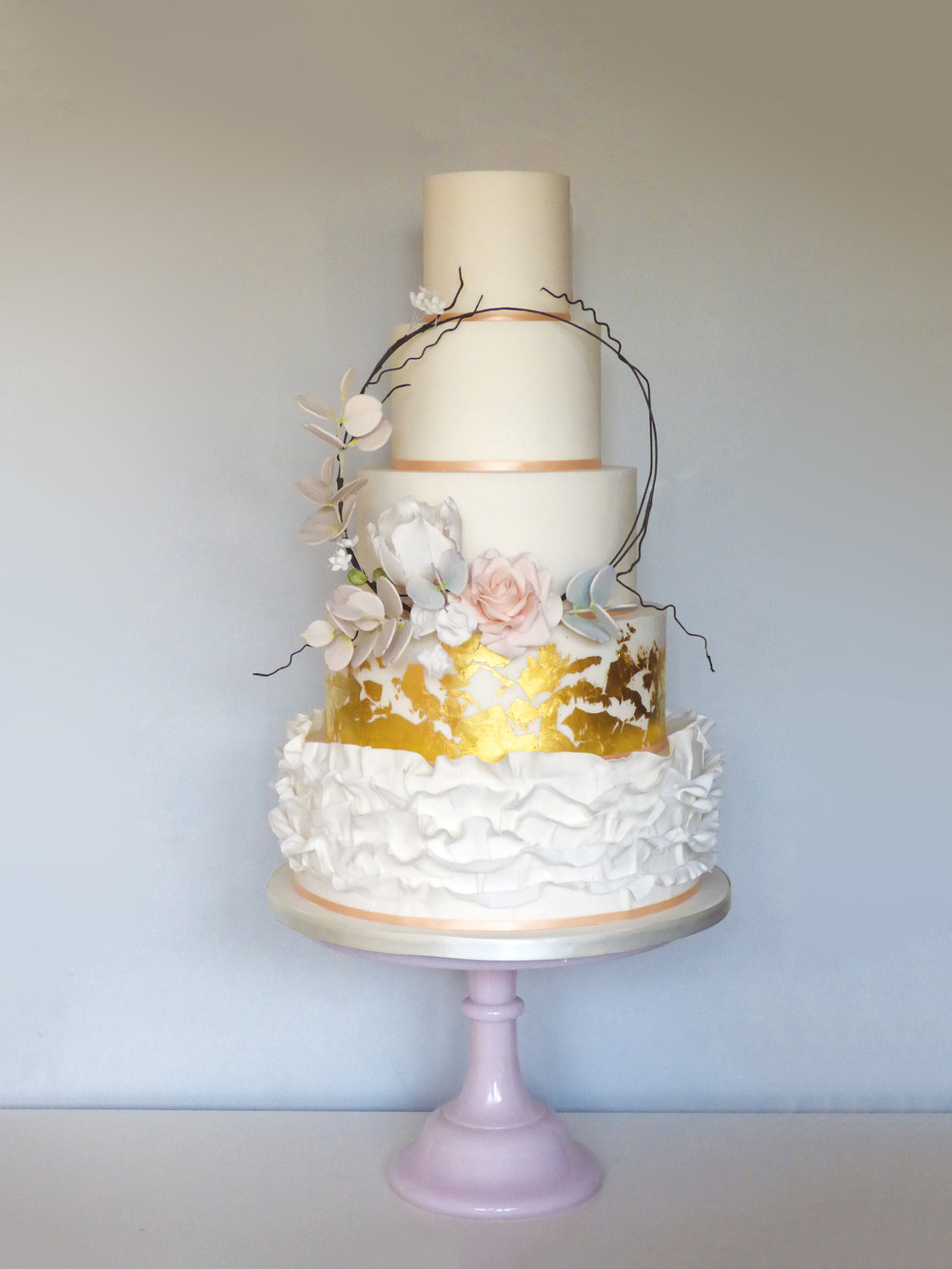 An ethereal, pretty wedding cake with light frills and gold leaf and a floral hoop for boho weddings or enchanted woodland themes.
