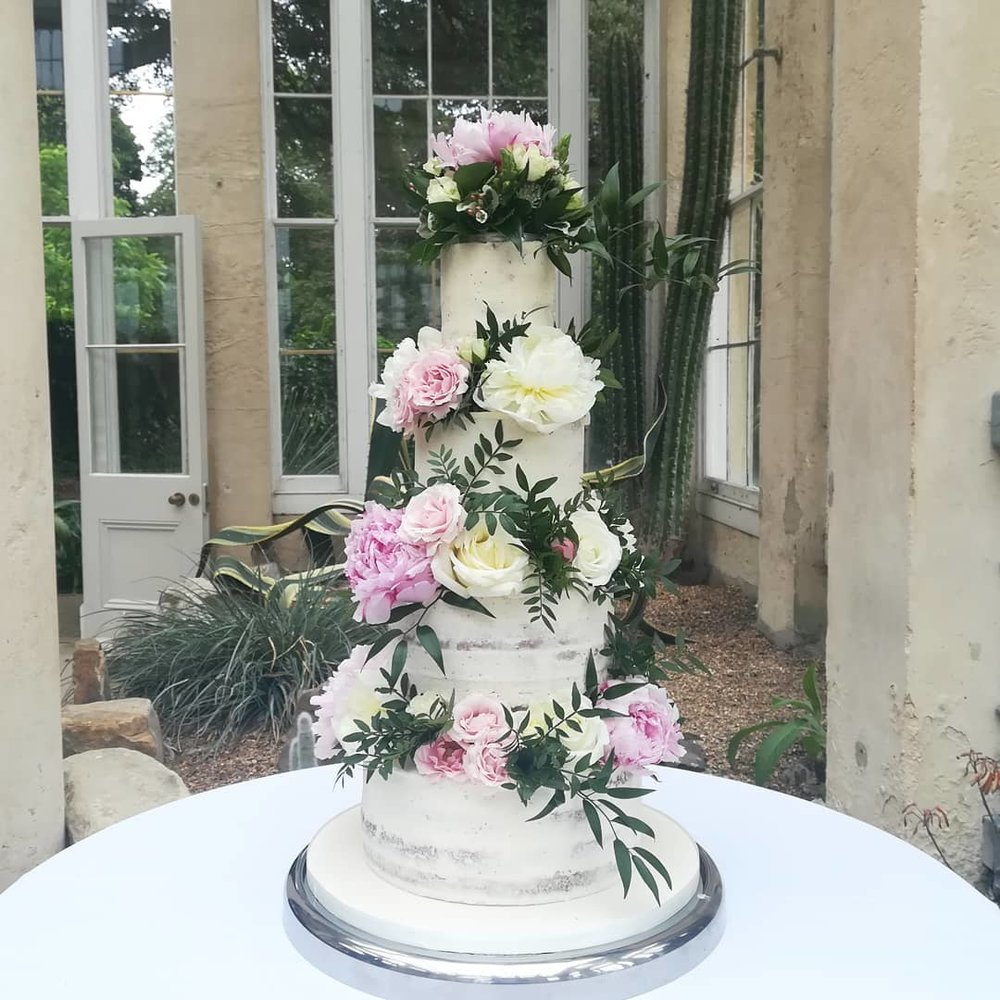 Semi naked wedding cake with fresh flowers and foliage at Syon House in west London