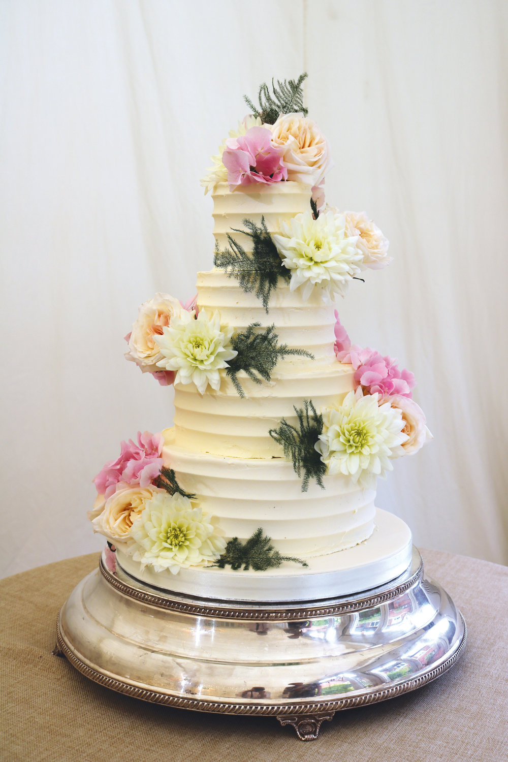 Buttercream covered wedding cake with a ridged or striped finish for a rustic look that's great on a budget! Shown here at Fulham Palace