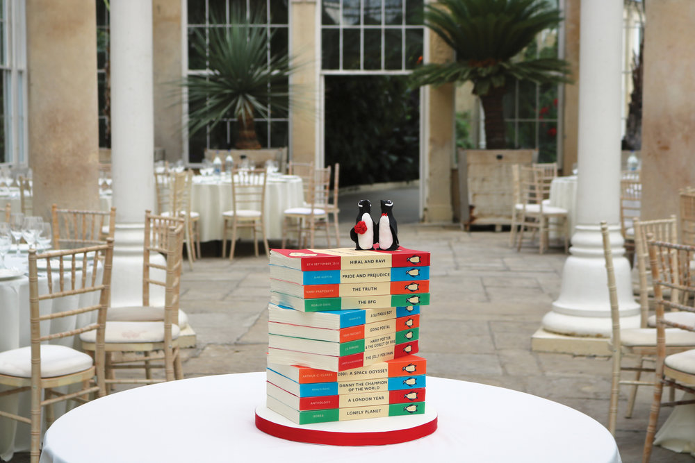 An illusion wedding cake that looks like a pile of penguin classic novels, perfect for book lovers! Here in the conservatory at Syon House.