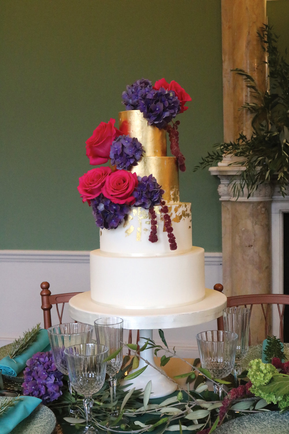 Gold leaf and fresh flowers on this wedding cake at Gunnersbury Park in Ealing