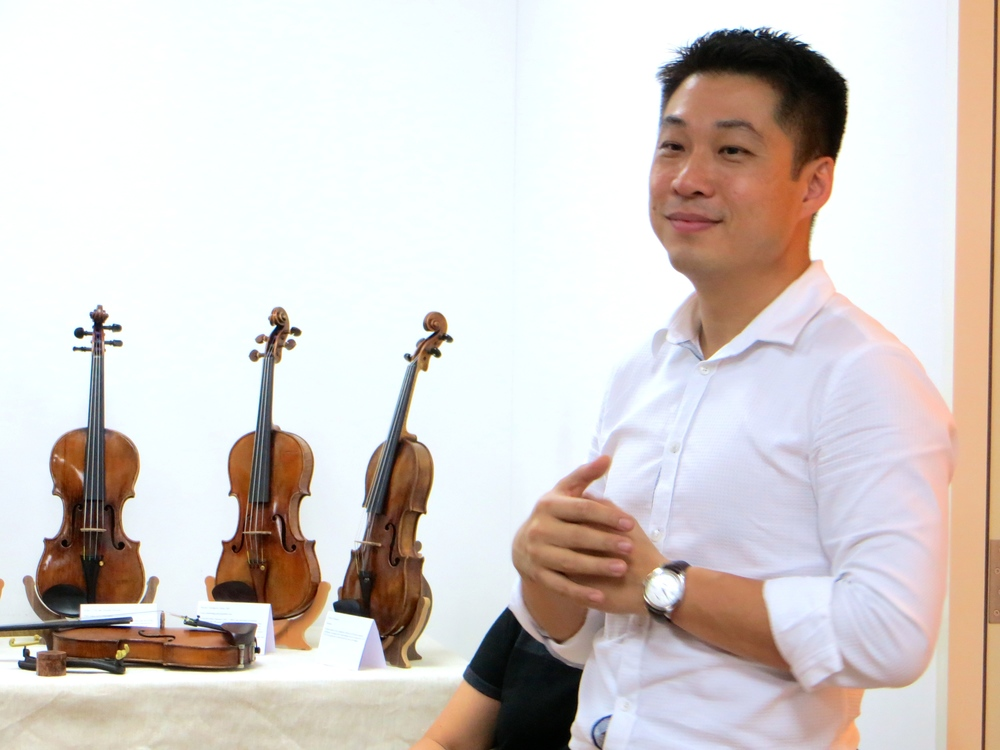 Guest Speaker Tong Mingxi giving tips on listening to the tone of a violin and what to look out for when purchasing a fine instrument