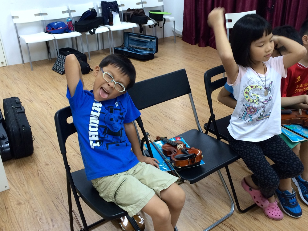 Our students, exhausted from 3 hours of intense violin playing and their messy bags in the background!