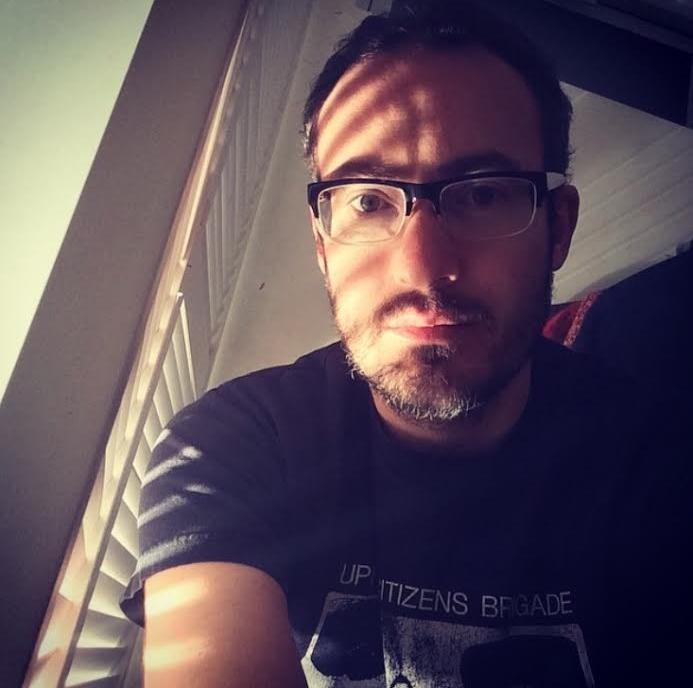 Director Brandon Bassham wearing an Upright Citizens Brigade t-shirt in a closet.