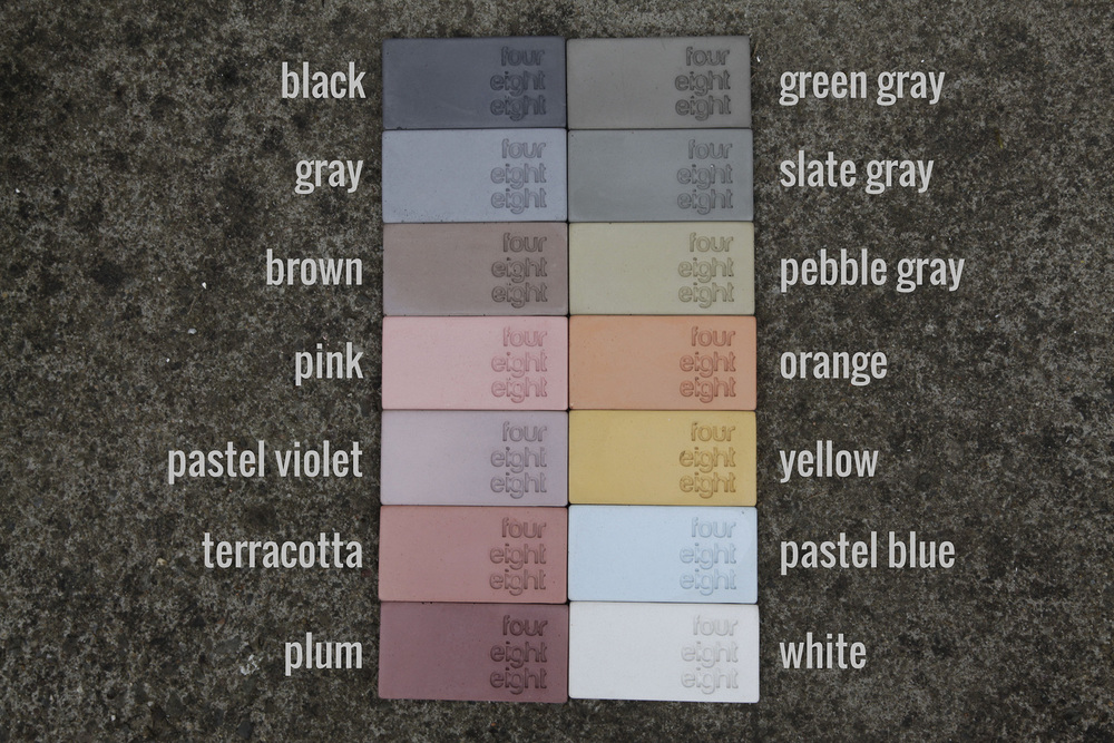 A Range of coloured concrete samples black gray brown pink violet terracotta plum green gray slate gray pebble gray orange yellow pastel blue white