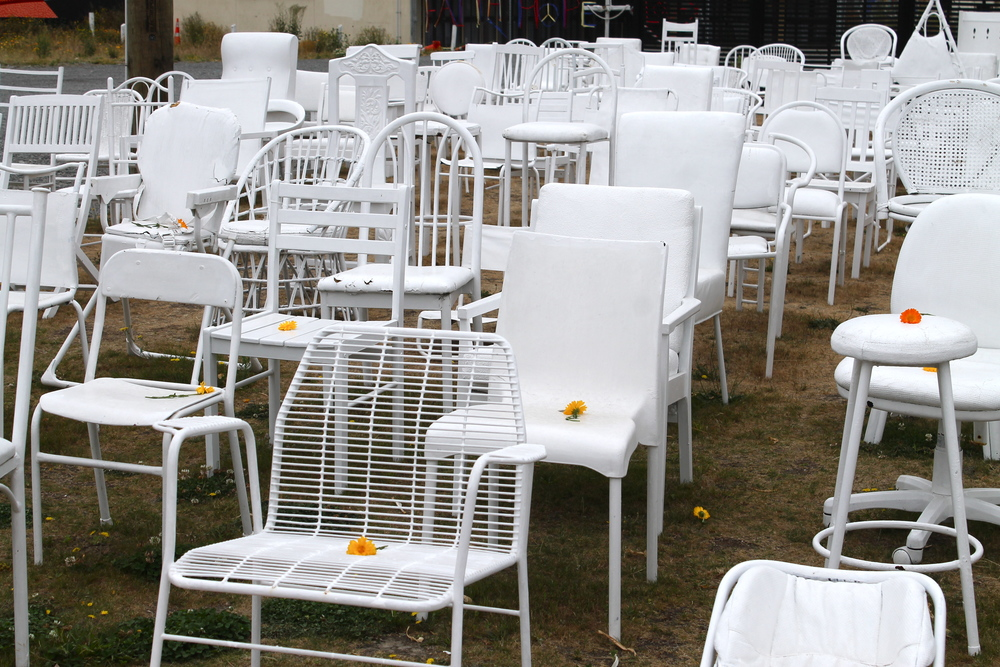 185 white chairs in honor of all the 185 people who were lost in the earthquake. A single flower on each.