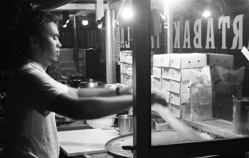 Street vendor preparing a Martabak. There's also a fried banana cart nearby, which makes for a perfect amuse-bouche while you're waiting.