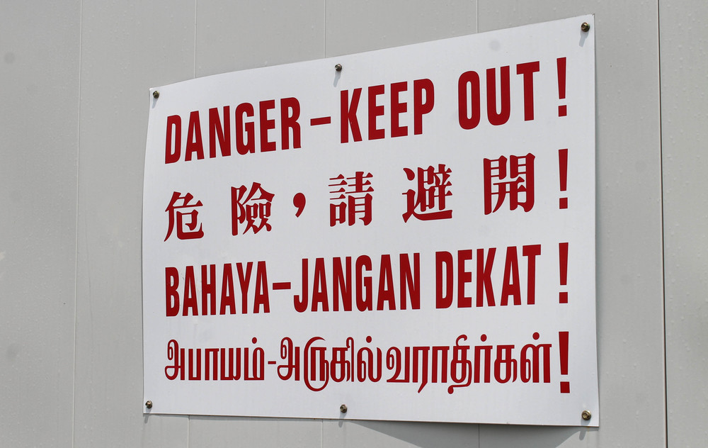Left: multi-lingual danger sign. Right: Sign on the subway banning durians, which are extremely smelly fruits. For real.