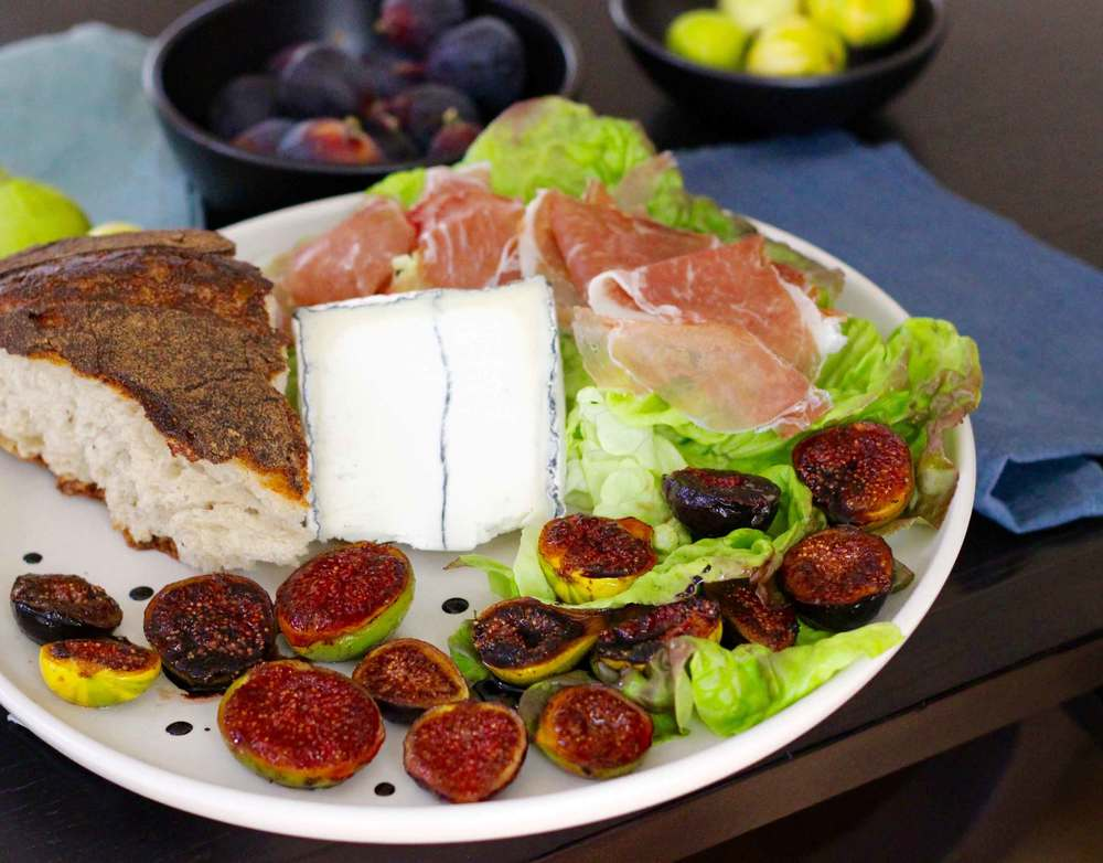 An appetizer platter lined with a bit of lettuce, prosciutto, a wedge of goat cheese, bread, and pan-seared figs with a balsamic reduction. Recipe at ThreadandWhisk.com.